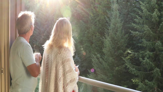 couple walk onto outdoor deck holding hot drink and smart phone - shawl stock videos & royalty-free footage