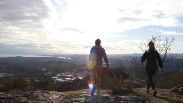 vídeos de stock e filmes b-roll de couple walk onto rock summit, overlooking city - distante