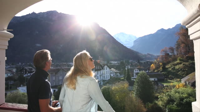 Couple walk onto terrace, look out at mountain view