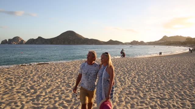 couple walk onto uncrowded beach, looking out to sea - パレオ点の映像素材/bロール