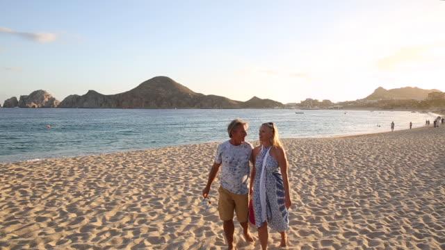 vídeos y material grabado en eventos de stock de couple walk onto uncrowded beach, looking out to sea - rosa brillante
