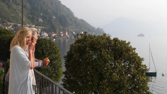 couple walk onto veranda at sunrise - piemonte video stock e b–roll