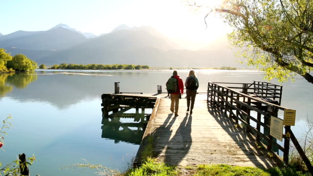couple walk out onto a dock at sunrise - coppia di età matura video stock e b–roll