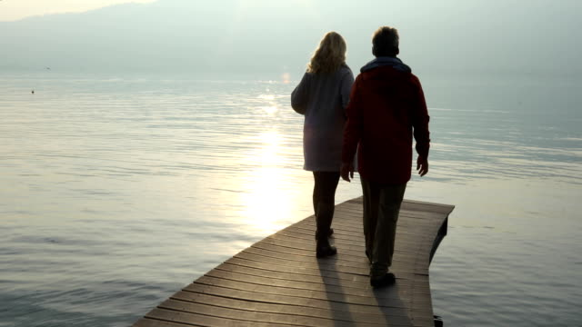 couple walk out onto atmospheric lake dock to admire tranquil mountain view - see other clips from this shoot 56 stock videos & royalty-free footage
