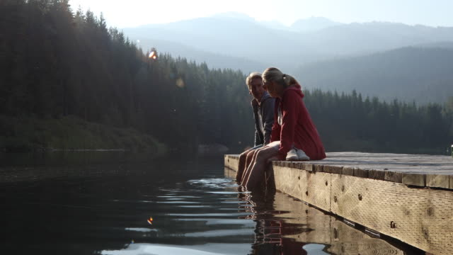couple walk out onto pier at sunrise, in mountains - pier stock videos & royalty-free footage