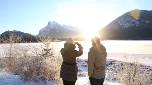 Couple walk out to edge of frozen lake, take smart phone pic