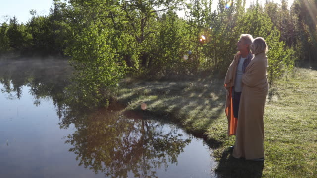 couple walk out to lake edge, wrapped in blanket - blanket stock videos & royalty-free footage