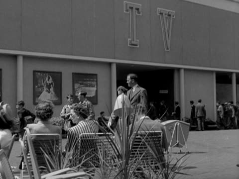 a couple walk past the television pavilion and the telekinema theatre at the festival of britain site on the south bank of the river thames 1951 - festival of britain stock videos & royalty-free footage