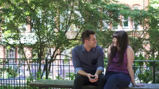 vídeos de stock e filmes b-roll de ts - couple walk, sit on bench and talk - banco de parque