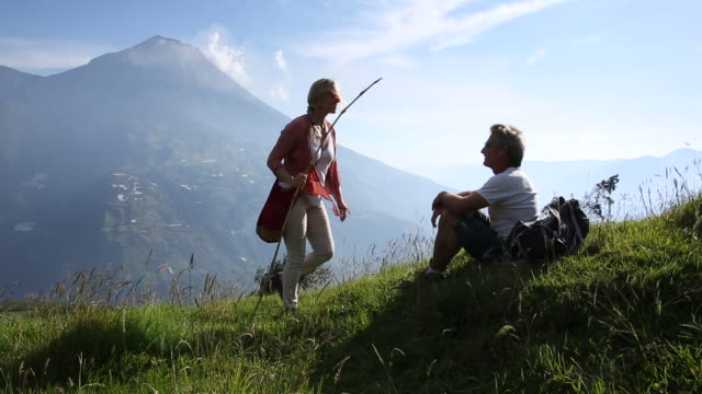 couple walk through alpine meadow below volcano, then relax - sitting stock-videos und b-roll-filmmaterial
