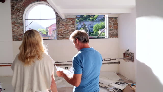 Couple walk through apartment during restoration process