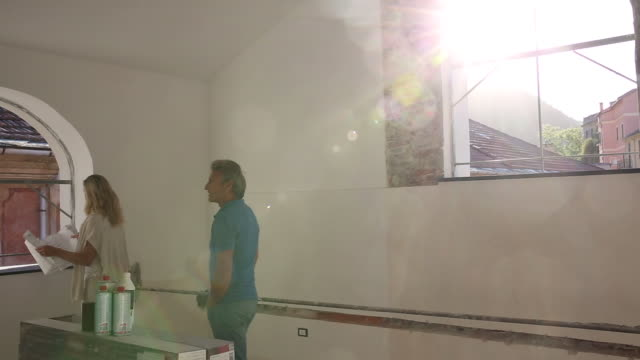 Couple walk through apartment during restoration process