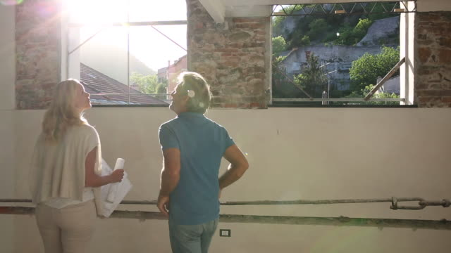 couple walk through apartment during restoration process - arco architettura video stock e b–roll