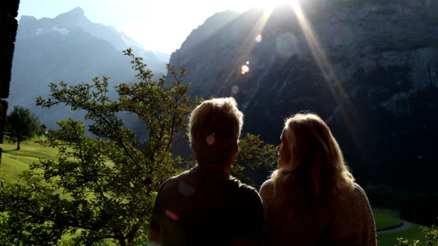 couple walk through doorway, look out to mountains - sehen stock-videos und b-roll-filmmaterial