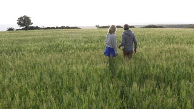 Couple walk through grain field, before harvest