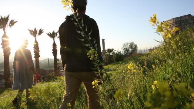 couple walk through green meadow, mosque in distance - 腰に手を当てる点の映像素材/bロール