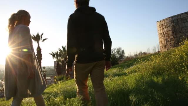couple walk through green meadow, mosque in distance - gå tillsammans bildbanksvideor och videomaterial från bakom kulisserna