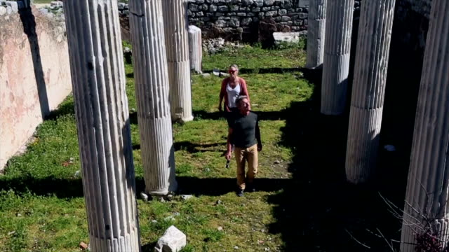 vídeos y material grabado en eventos de stock de pareja a pie a través de columnas de mármol, explorar - encontrar