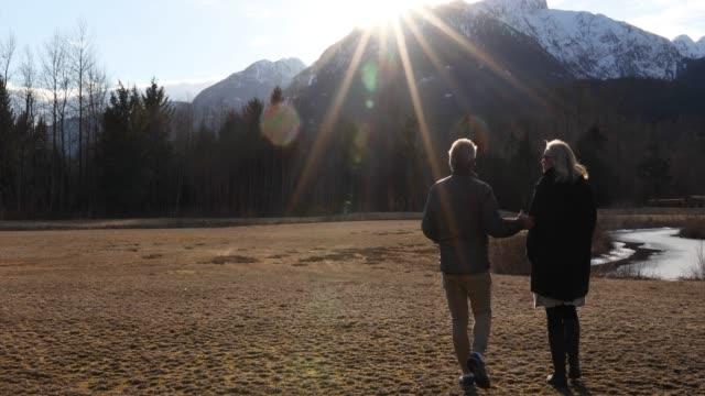 vidéos et rushes de promenade de couples à travers le glade de montagne au lever du soleil - lockdown
