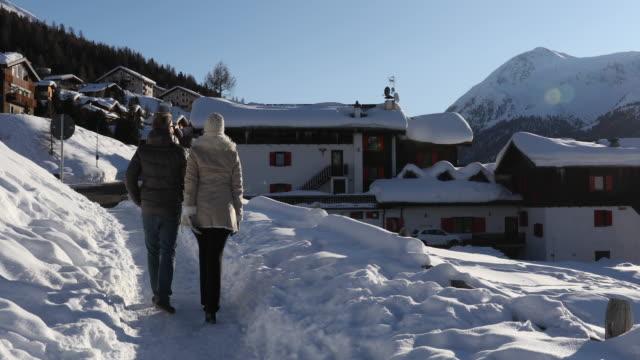 Couple walk through snow towards mountain village