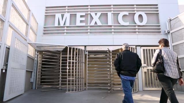 a couple walk through the border gate into mexico on april 9 2018 in san ysidro california - zoll und einwanderungskontrolle stock-videos und b-roll-filmmaterial