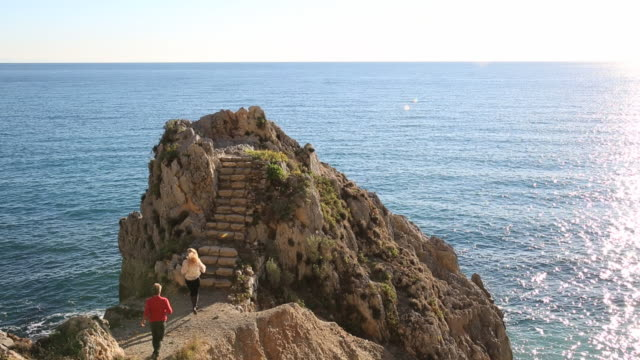 vidéos et rushes de couple walk up rock steps on buttress above sea - marches et escaliers