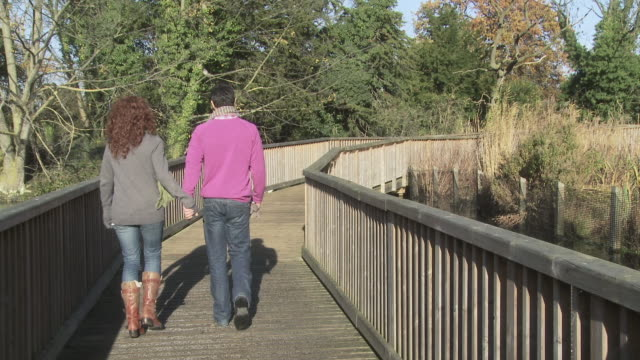 Couple walking across bridge hand in hand