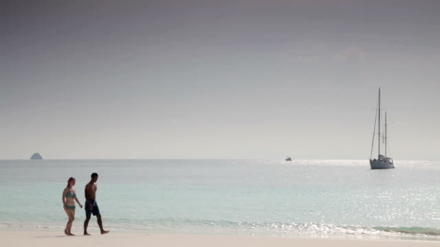 couple walking along a beach on a sailing holiday - myanmar stock videos & royalty-free footage