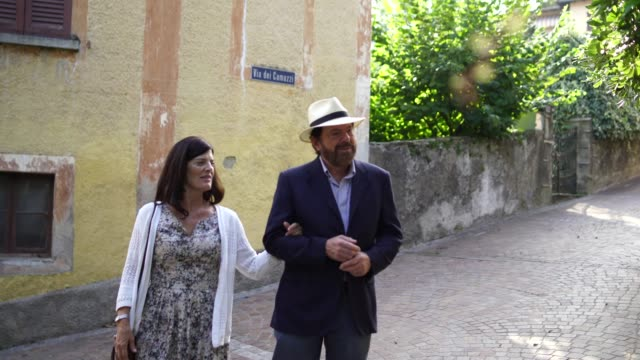 couple walking along an old street in a mediterranean town - guidance stock videos & royalty-free footage