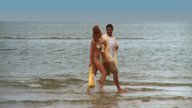 ms pan couple walking along beach in shallow water, eastville, virginia, usa - eastville stock videos and b-roll footage