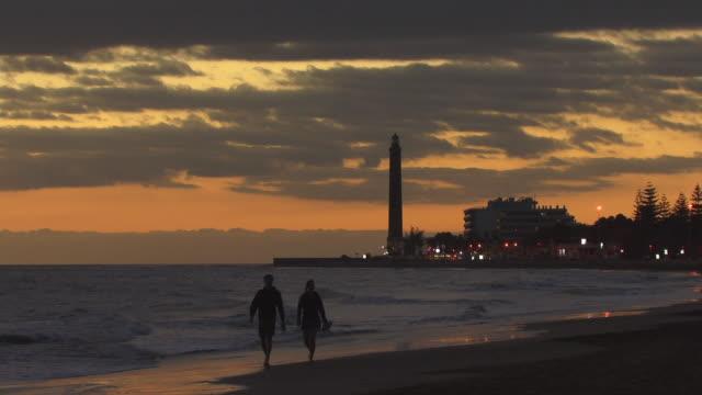 ws zo zi couple walking along beach near lighthouse at sunset / maspalomas, gran canaria, spain - spain stock videos & royalty-free footage
