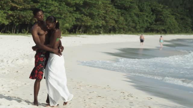 ms couple walking along beach, st. michael's, bridgetown, barbados - gemeinsam gehen stock-videos und b-roll-filmmaterial