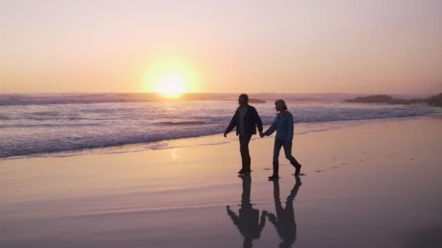 vídeos de stock e filmes b-roll de couple walking along beach together at sunset holding hands - cena de tranquilidade