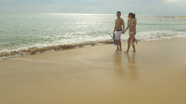 Couple walking along beach with snorkel gear in tropical climate