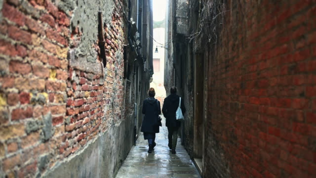 Couple walking along narrow street