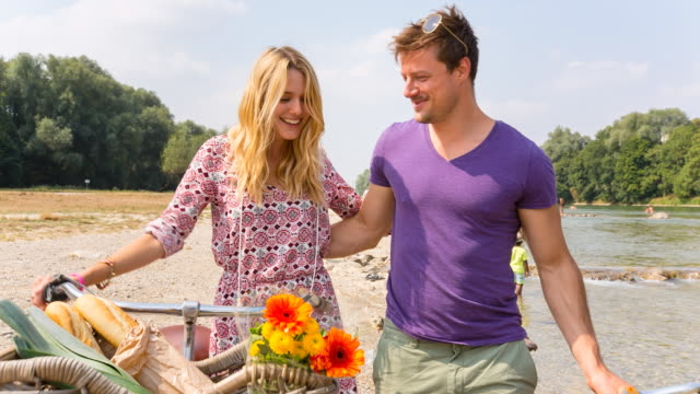 couple walking along river shore - korb stock-videos und b-roll-filmmaterial