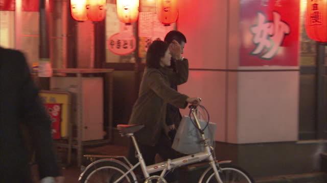 ws pan couple walking along street with bike, tokyo, japan - zona pedonale strada transitabile video stock e b–roll
