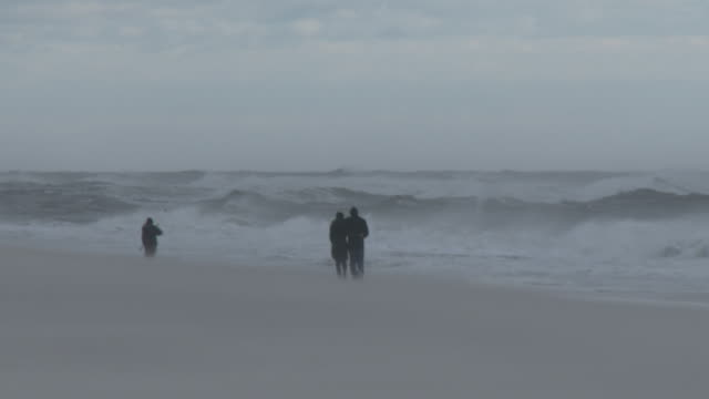 A couple walking along the shoreline at Jones Beach on Long Island are barely visible as powerful gale force winds blow sand around and create very...
