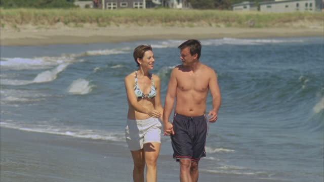 WS CU Couple walking along water's edge on beach then boy and girl splash them / Phippsburg, Maine, USA