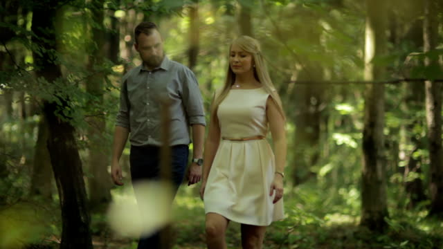 MEDIUM SHOT TRACKING SHOT Couple walking and flirting in forest on sunny day
