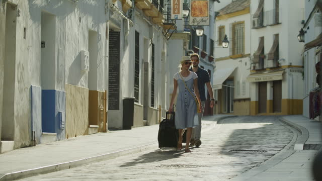 couple walking and pulling suitcases downhill to hotel in city / cordoba, cordoba, spain - full length stock-videos und b-roll-filmmaterial