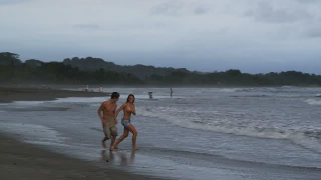 couple walking and running on the beach - 恋に落ちる点の映像素材/bロール