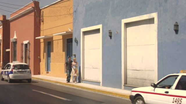 vídeos y material grabado en eventos de stock de ws couple walking and talking along busy street / merida, mexico  - mérida méxico