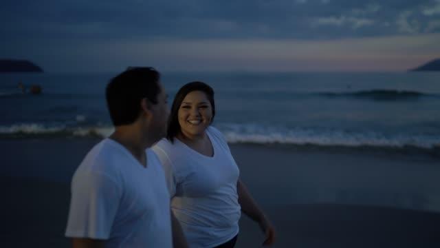 vídeos de stock, filmes e b-roll de passeio dos pares no tempo do por do sol na praia - discovery