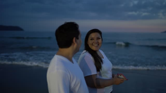 couple walking at sunset time on the beach - plus size model stock videos & royalty-free footage