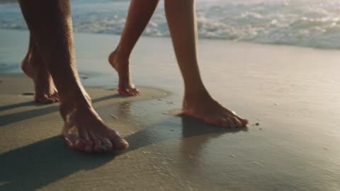 stockvideo's en b-roll-footage met paar wandelen op het strand - barefoot