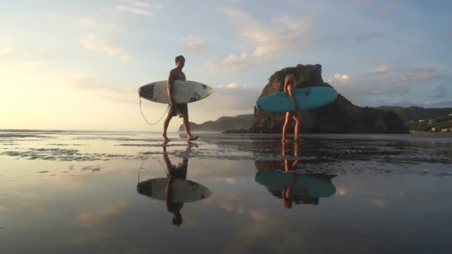 couple walking back home after surfing. - new zealand stock videos & royalty-free footage