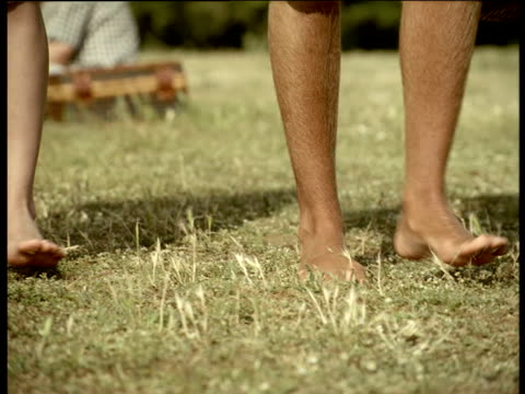 couple walking barefoot on grass stop to lay blanket on ground and sit down for picnic england - bedclothes stock videos & royalty-free footage