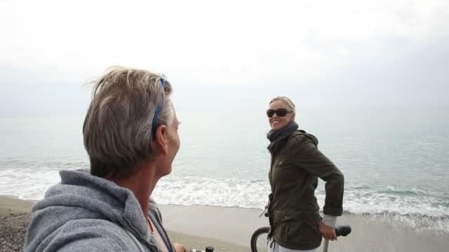 vídeos de stock e filmes b-roll de pov of couple walking bikes along beach at surf edge - homens adultos