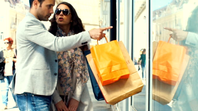 Couple walking by retail stores.